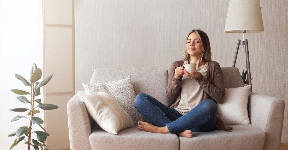 woman peacefully resting on couch with coffee and eyes closed, prayers to rest in the Lord