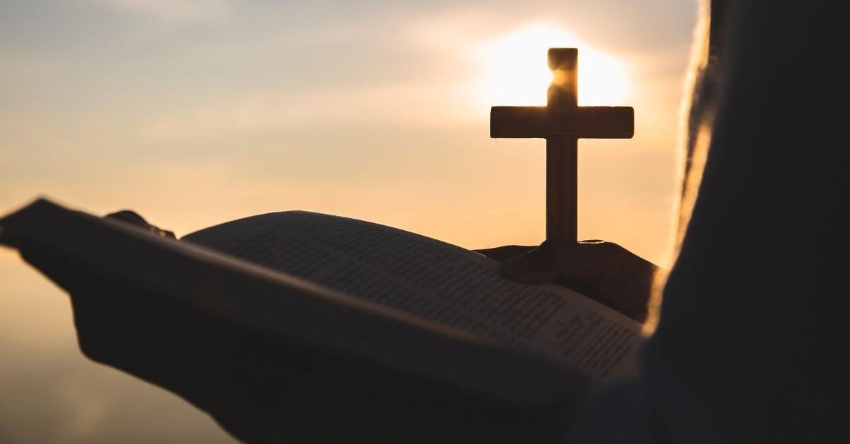 open bible holding bible reading cross sunset sunrise