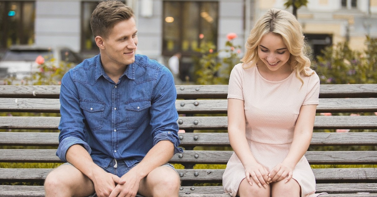 guy and girl smiling flirting on a date sitting on a bench, relationship boundaries