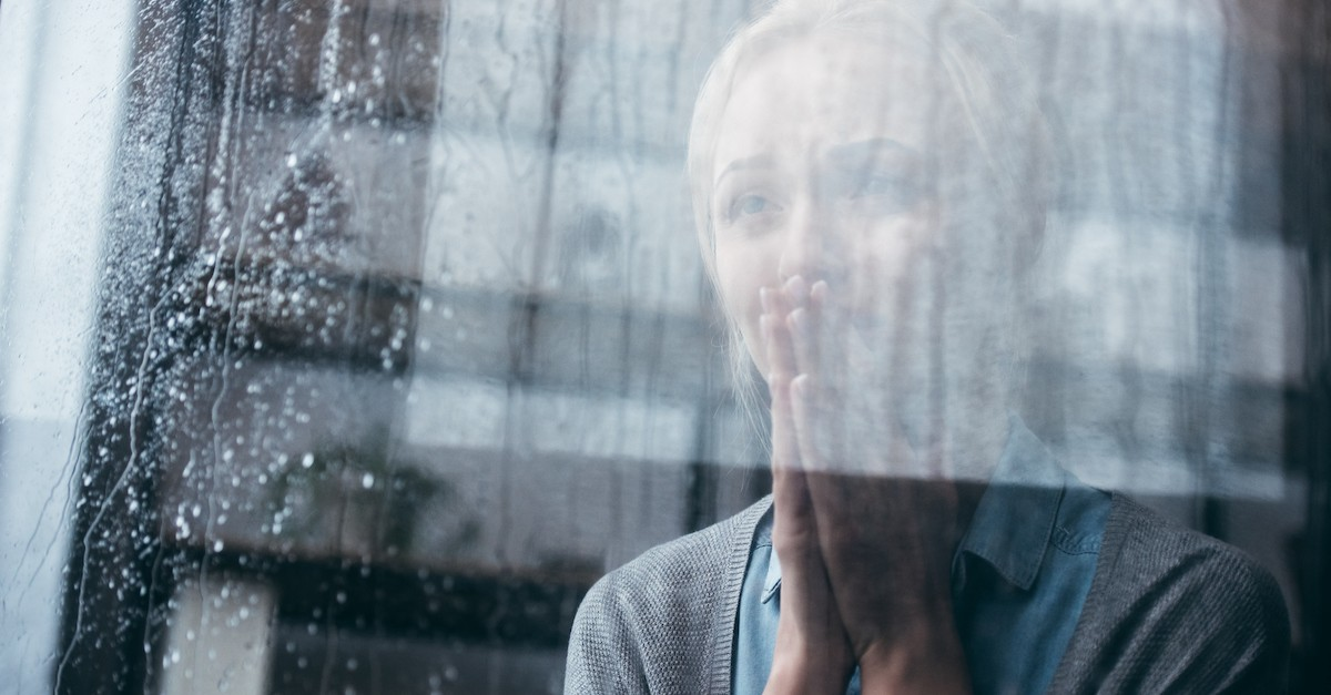 woman looking out of window in the rain, who was rizpah