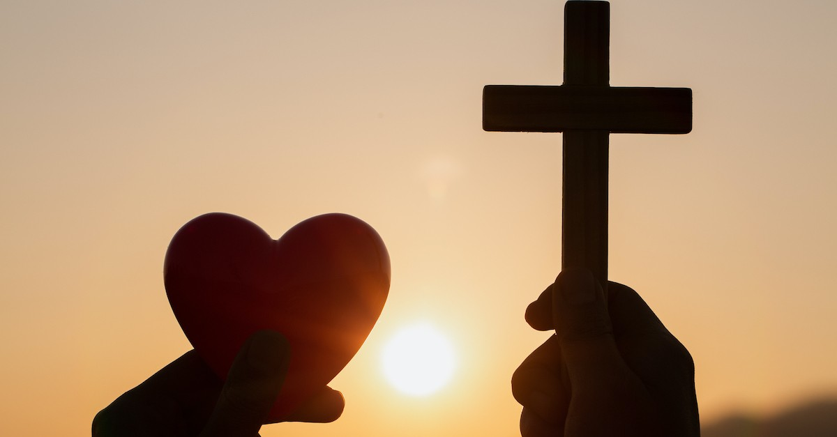 silhouette of hands holding up a heart and a cross outside at sunset, love your enemies