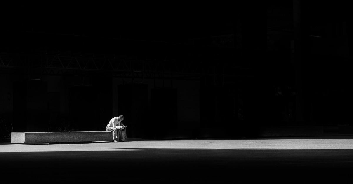 Man sitting alone in a dark space