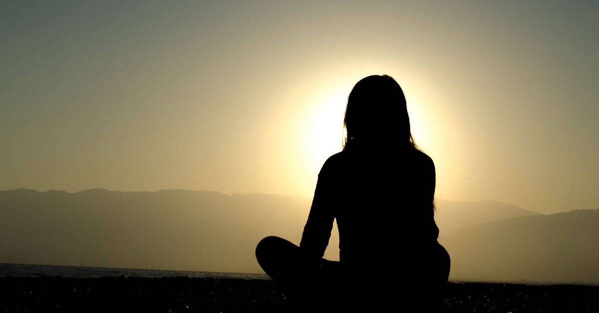 Silhouette of a peaceful woman sitting outside