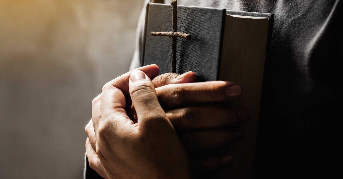 Hands holding a Bible and wooden cross