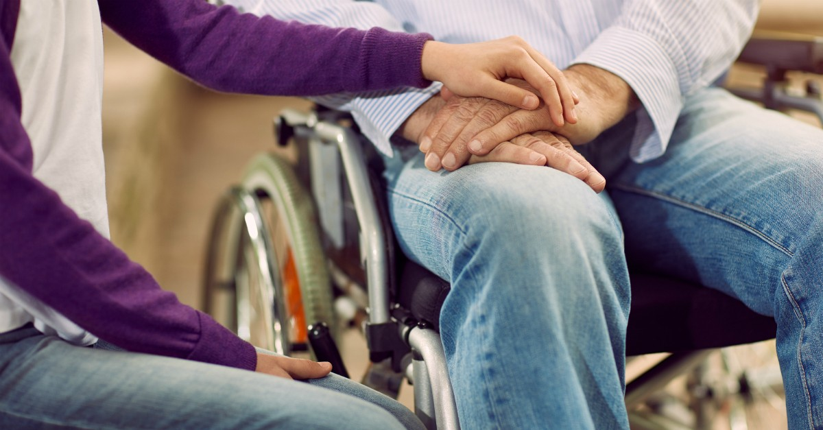 Someone holding the hand of a man in a wheelchair