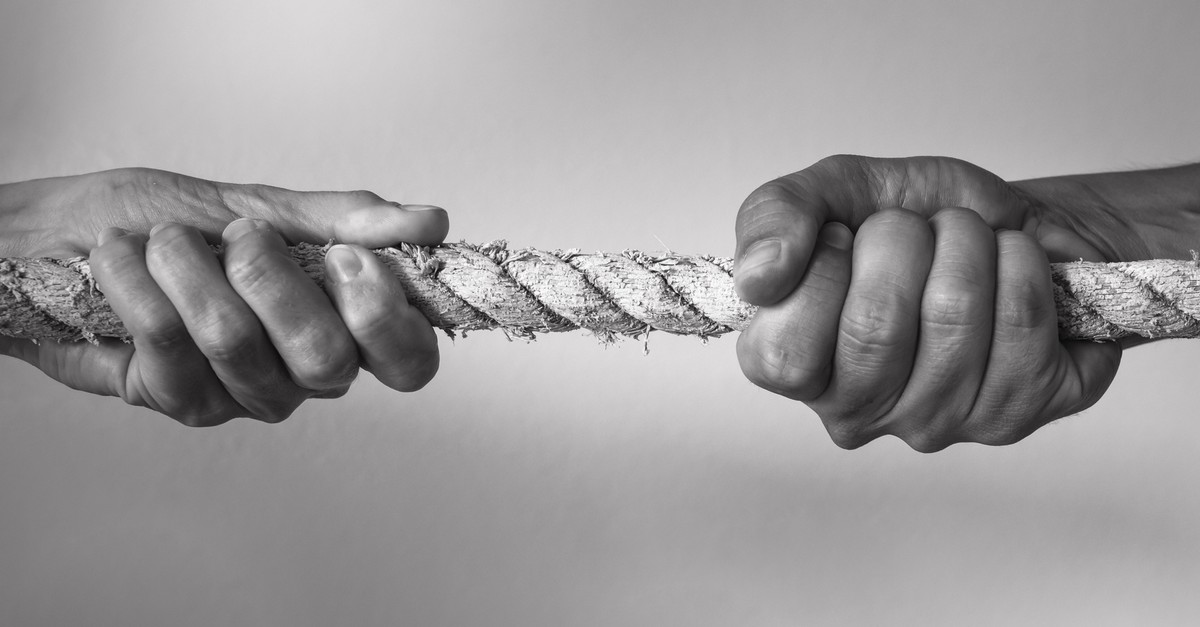 Two people pulling opposite ends of a rope