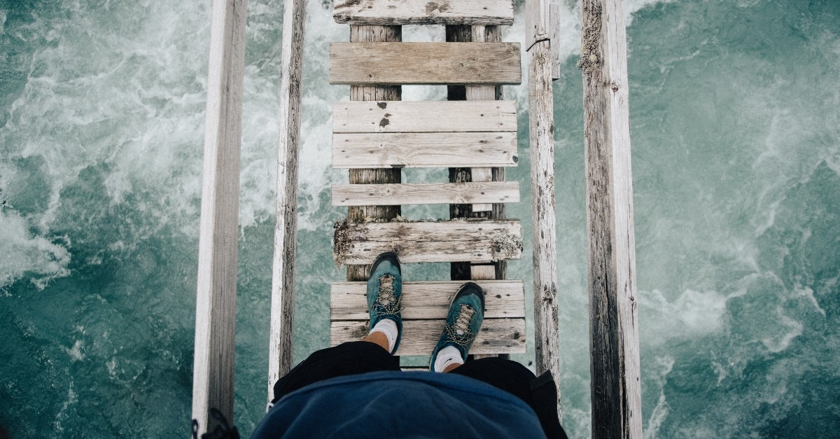 Shot of a person's feet on a rickety bridge over running water