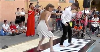 Couple Plays Floor Piano with Synchronized Dance