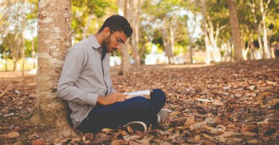 Man reading his Bible under a tree