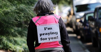 A woman walking with an I'm praying for you sign, National Day of Prayer