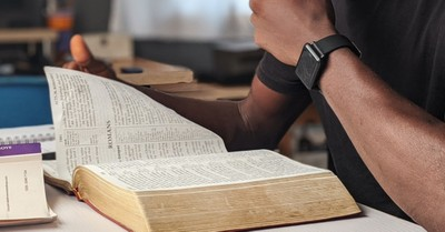 A man reading a Bible, man argues that protesting isn't going to change anything