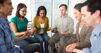 diverse group of adults in prayer circle together unity