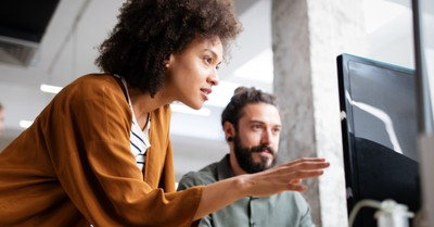 diverse woman and man working together at computer