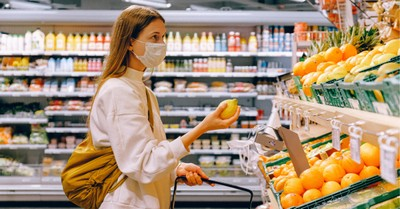 A woman wearing a mask in a store, Why America is so conflicted over the pandemic