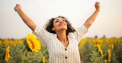 happy and joyful woman with arms in the air in a sunflower field, prayers of joyful defiance in tired world
