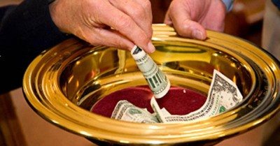Someone putting money in an offering plate, giving back up months into the pandemic