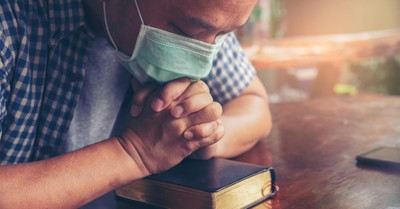 man in face mask praying on bible for pastor appreciation month