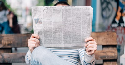 A person reading a newspaper, top news stories of 2020