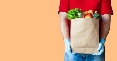 A Man holding a bag of food, 76 percent of people want to focus on those in need this Christmas