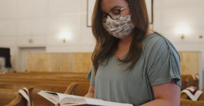 A woman in church wearing a mask, California changes their indoor worship services rules