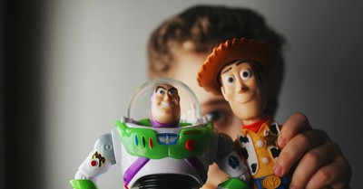 A kid holding a Buzz Lightyear and Woody toy, steps to relationships that transform