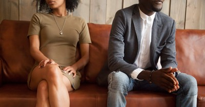 Couple separated on a couch, Christian relationship guru admits to cheating on his wife multiple times