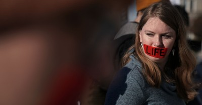 A woman with red tape over her mouth that features the word 'Life', pro-life democrats fight for the Hyde Amendment