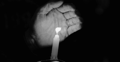 A memorial candle, hundreds attend memorial for Tulsa Race Massacre