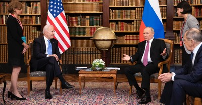 Biden and Putin sitting in a library during the Geneva Summit, Biden gives Putin a list of US infrastructure entities that are 'off-limits' to cyber attacks
