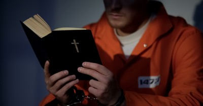 Inmate reading the Bible, Prison fellowship and Moody Bible Institute to distribute 100,000 devotionals to inmates