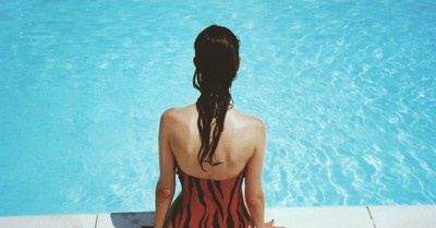 A woman on a pool side, Pastor apologizes for requiring girls to wear a one piece bathing suit