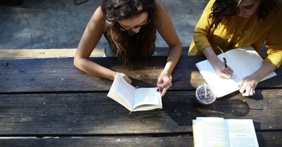 Girl reading at a table, Court rules with InterVarsity in case against University of Iowa