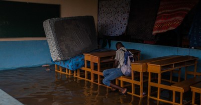 A young boy sitting in a destroyed and flooded school, Haiti is hit by a tropical storm just days after experiencing a 7.2 magnitude earthquake