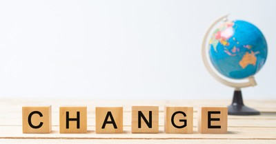 """A globe with scrabble tiles in front of it spelling """"Change"""""""