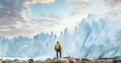 A lone hiker stands gazing at a glacier in the far north