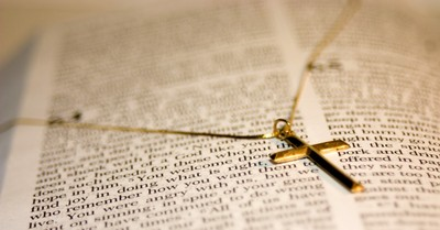a gold cross necklace on a Bible, nurse fired for refusing to remove her cross necklace sues her former employer