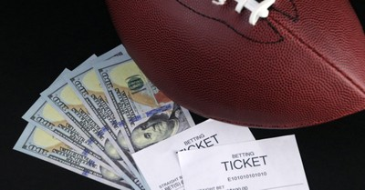 A football with money and sports betting tickets, the rise of sports gambling