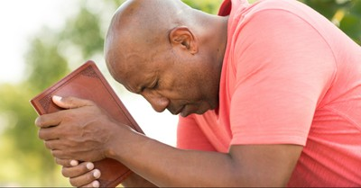 a man praying and holding a Bible, Trusting God in our suffering