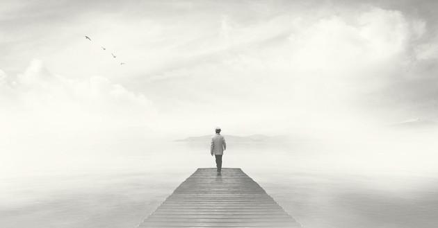 man walking on gray bridge with gray background, depression