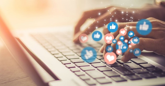 closeup of hands typing away on laptop with social media icons floating up from keyboard