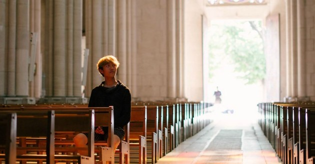 young man sitting alone in empty church sanctuary looking up, shadow of person walking through sunlit doorway behind him