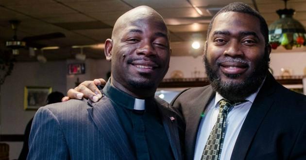 man shoulder-hugging pastor, both smiling proudly