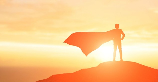 silhouette back view man facing sunrise on mountain, superhero cape blowing in wind