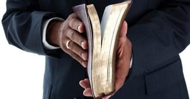 closeup of man's hands holding open Bible