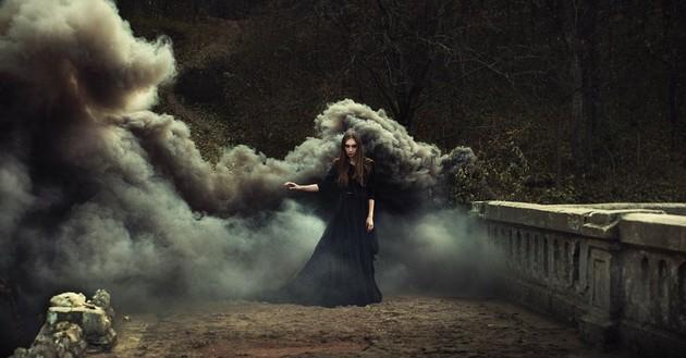 woman wearing black dress in smoke-filled woods