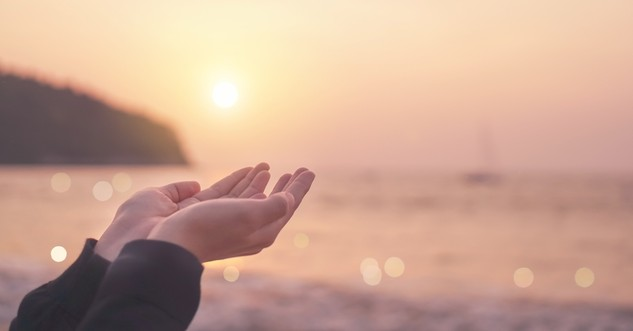 holding open hands up to soft light sunset - do this in remembrance of me