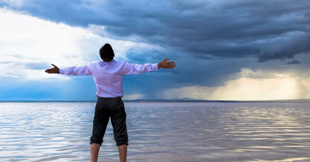 Man standing before a storm, questioning God