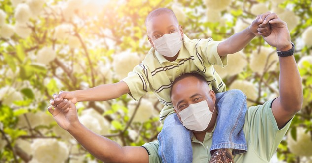 dad with son on shoulders both wearing face masks for coronavirus