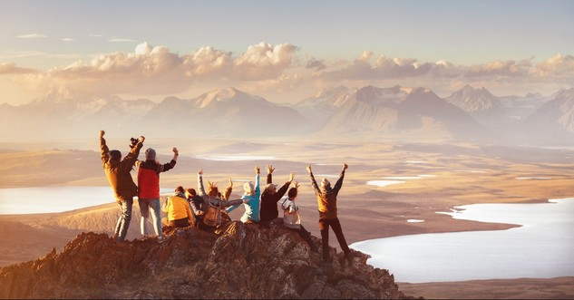 People cheering on top of a mountain