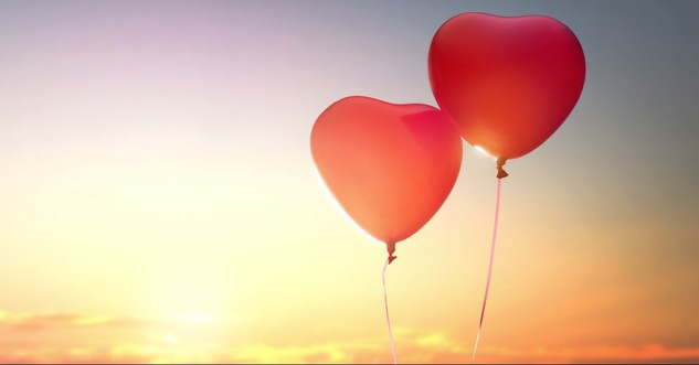 Two heart balloons in the sunset